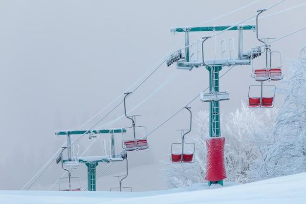 Winterurlaub im skigebiet berge. die unterstützung des lifts ist im morgengrauen mit schnee und frost bedeckt. wunderbare landschaft bei sonnenuntergang.