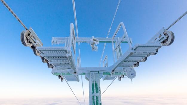 Winterurlaub im skigebiet berge. die unterstützung des lifts ist im morgengrauen mit schnee und frost bedeckt.