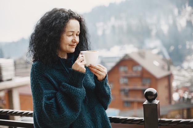 Winterurlaub in den bergen. lockiges haar bei frauen. weiße tasse mit kaffee.
