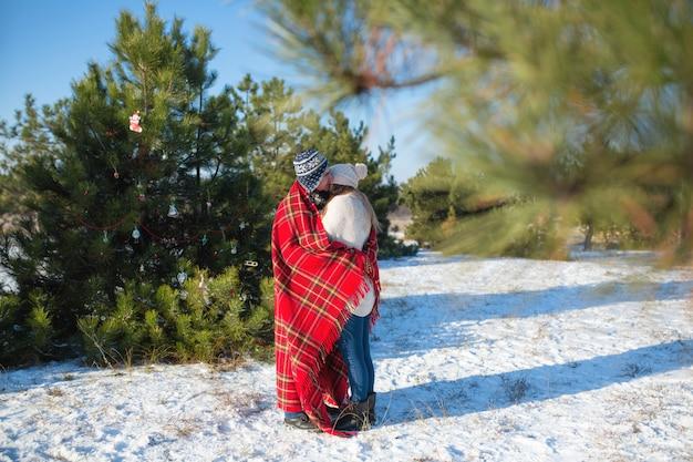 Winterwanderung durch den wald. der mann in der roten plaiddecke wickelt das mädchen ein, damit es warm wird