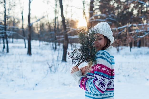 Winterwanderung. junge frau, die tannenbaumaste im wald genießt schneewetter in gestrickter strickjacke hält