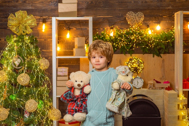 Winterweihnachtsgefühlskind mit teddybär auf holzhaushintergrundporträt von santa kind look...