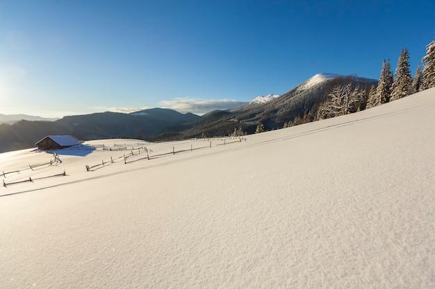 Winterweihnachtslandschaft des gebirgstals am frostigen sonnigen tag. alte hölzerne verlassene hirtenhütte im weißen tiefen sauberen schnee, holziger dunkler gebirgskamm, helle sonne auf blauem himmel kopieren raumhintergrund.