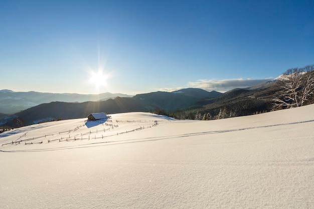 Winterweihnachtslandschaft des gebirgstals an einem frostigen sonnigen tag. alte hölzerne verlassene hirtenhütte im weißen tiefen sauberen schnee, waldiger dunkler bergrücken, helle sonne auf kopienraumhintergrund des blauen himmels.