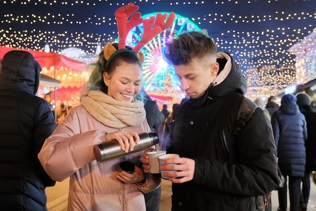 Winterweihnachtsporträt des glücklichen paares am feiertagsmarkt, lachende teenager, die heißen tee von der thermoskanne gießen