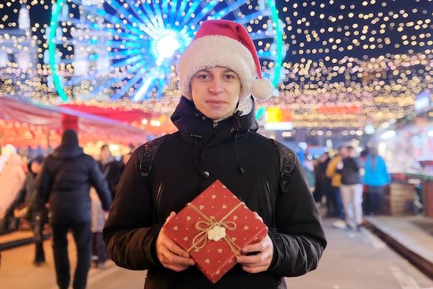 Winterweihnachtsporträt des glücklichen teenagers mit geschenkbox am feiertagsmarkt der stadt im freien
