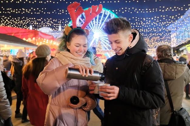 Winterweihnachtsporträt eines glücklichen jugendlichen jungen und mädchens am feiertagsmarkt