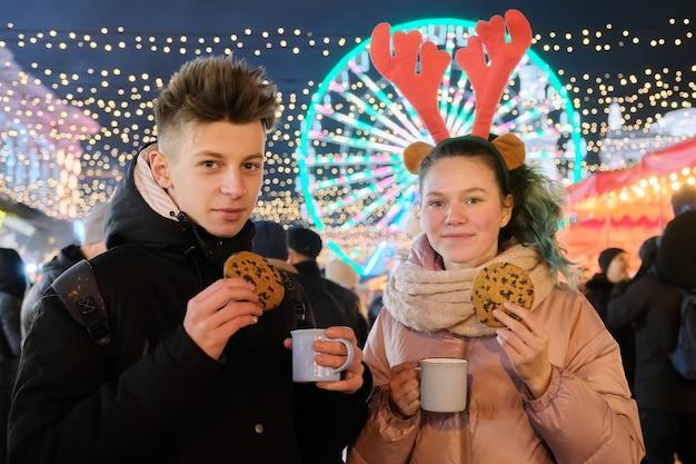 Winterweihnachtsporträt eines glücklichen paares am feiertagsmarkt