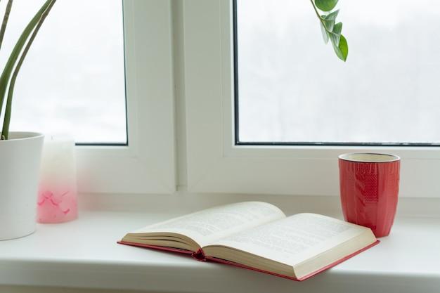 Winterzeit, schneebedecktes fenster, ein offenes buch und eine tasse mit einem heißen getränk