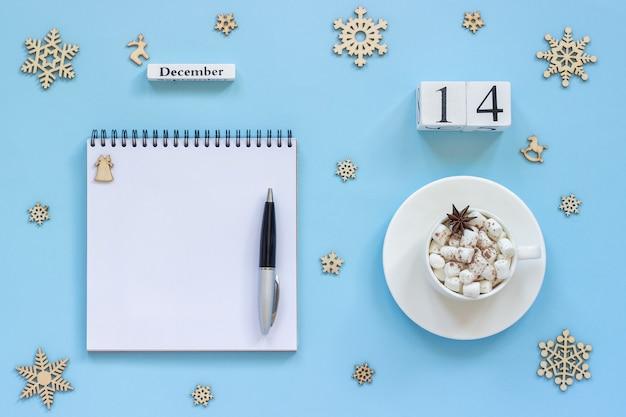 Winterzusammensetzung. holzkalender 14. dezember tasse kakao mit marshmallow und sternanis, leerer offener notizblock mit stift und schneeflocke auf blauem hintergrund. draufsicht flaches mockup-konzept
