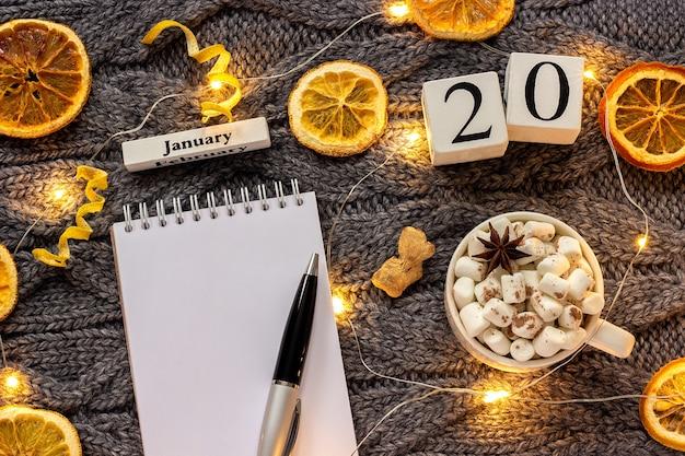 Winterzusammensetzung. holzkalender januar tasse kakao mit marshmallow, leerer offener notizblock mit stift, getrocknete orangen, helle girlande auf grauem gestricktem hintergrund. draufsicht flaches mockup
