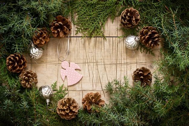 Winterzusammensetzung mit niederlassungen von wacholderbusch- und thuja- und weihnachtsspielwaren auf einem hölzernen hintergrund. rustikaler stil.
