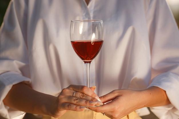 Winzerfrau, die rotwein aus einem glas in einem weinberg schmeckt. weinberge hintergrund bei sonnenuntergang. makroaufnahme einer sommelierhand, die das weinglas hält