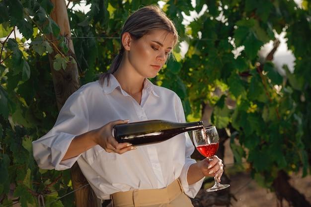 Winzerfrau, die rotwein aus einem glas in einem weinberg schmeckt. weinberge hintergrund bei sonnenuntergang.