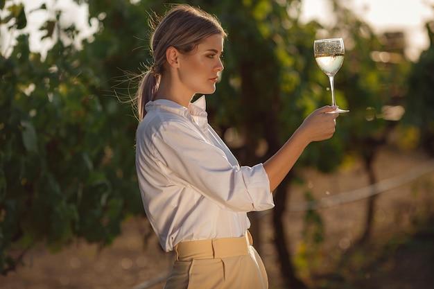 Winzerfrau, die weißwein aus einem glas in einem weinberg schmeckt. weinberge hintergrund bei sonnenuntergang.