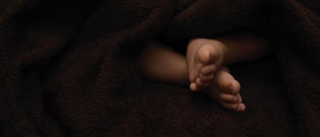 Winzige füße neugeborenes baby, dunkler hintergrund