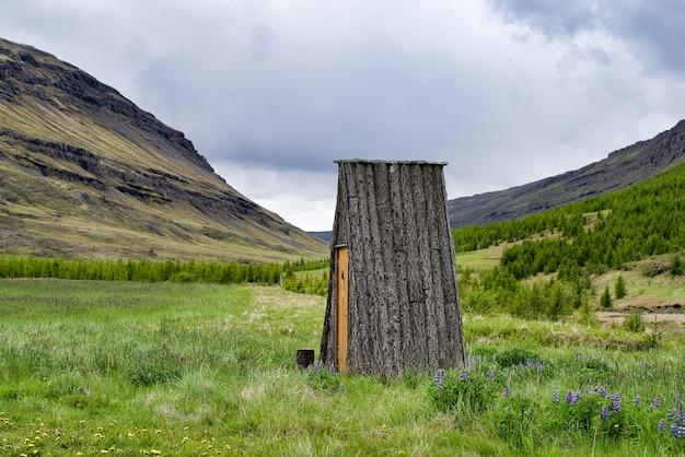 Winzige isländische blockhütte ohne fenster auf einer wiese neben bergen. ohne wände. nur dach.