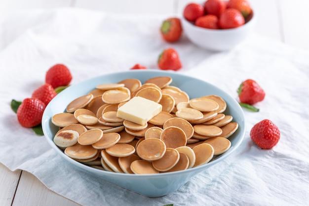 Winzige müsli-pfannkuchen in der blauen platte mit erdbeeren auf weiß