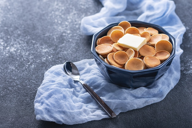 Winzige müsli-pfannkuchen mit butter in blauer schüssel, löffel auf blauer gaze auf grau