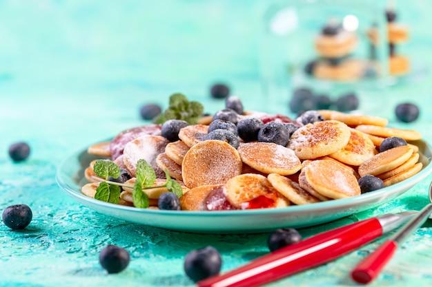 Winzige pfannkuchen mit frischen blaubeeren, minze und beerensirup