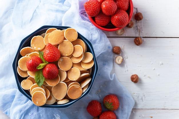 Winzige pfannkuchen müsli mit erdbeeren in der blauen schüssel auf blauer gaze auf weiß