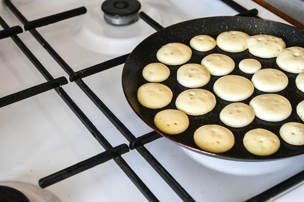 Winzige pfannkuchen müsli quarantäne trend essen. mini-pfannkuchen werden in einer pfanne in der küche gebraten. kochvorgang. live-foto braten