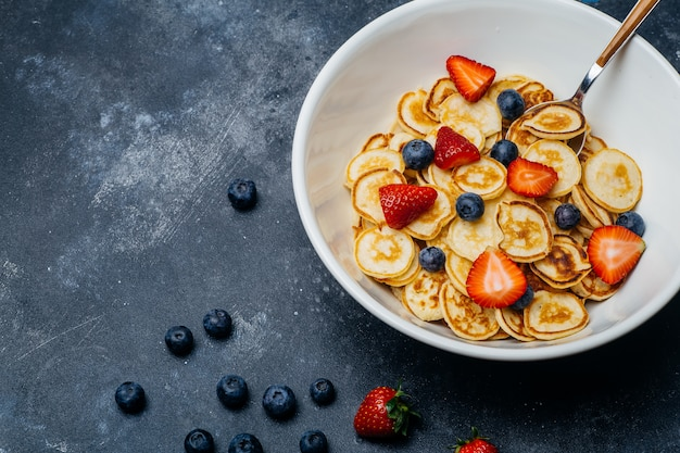 Winzige pfannkuchen zum frühstück. pfannkuchen mit erdbeeren und blaubeeren, die morgens zum frühstück in der wohnküche gekocht werden.