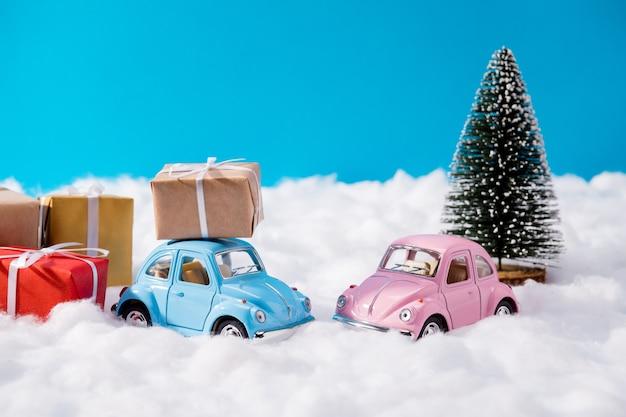 Winzige rosa und blaue autos und weihnachtsgeschenke
