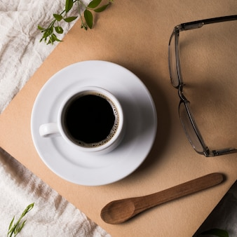 Winzige tasse kaffee auf teller und lesebrille