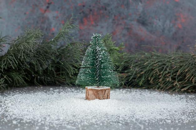 Winzige weihnachtsbaumfigur neben einem immergrünen ast auf marmoroberfläche