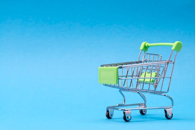 Winziger einkaufswagen auf dem blau