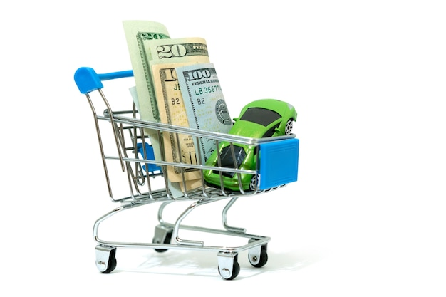 Winziger grüner sportwagen und amerikanische dollars in einem kleinen winzigen einkaufswagenwagen lokalisiert auf einem weißen hintergrund.
