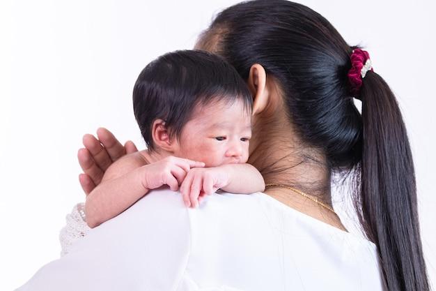 Winziges entzückendes neugeborenes baby wacht auf der schulter ihrer mutter auf