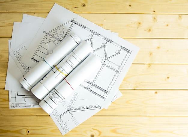 Wir bauen ein gebäude. hausbau. viele zeichnungen zum bauen auf einem hölzernen hintergrund.