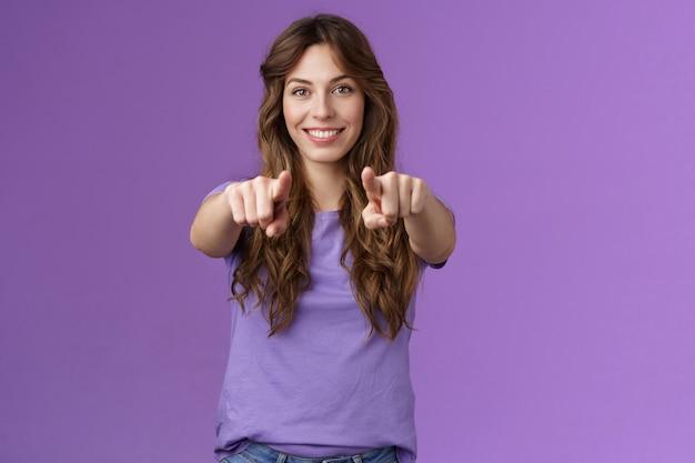 Wir brauchen dich in unserem team. durchgesetzte, selbstbewusste, gut aussehende büroleiterin, die neue leute rekrutiert, die neulinge suchen, die selbstbewusst mit den fingern der kamera auf violettem hintergrund lächeln