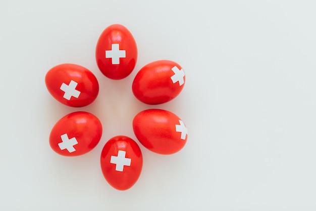 Wir feiern den schweizer nationalfeiertag am 1. august mit traditionellen eiern, die wie die schweizer flagge gefärbt sind. traditioneller brunch am gründungstag der schweizerischen eidgenossenschaft.