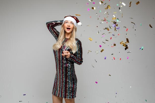 Wir feiern weihnachten und neujahr, junges schönes überraschtes mädchen in der weihnachtsmütze mit buntem konfetti und champagner.