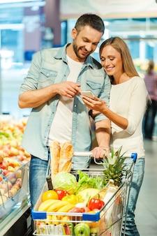 Wir haben alles gekauft, was wir brauchen. glückliches junges paar, das zusammen auf das handy schaut, während es in der nähe des einkaufswagens im lebensmittelgeschäft steht
