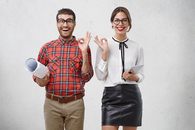 Wir haben es getan! erstaunte weibliche und männliche zeigen ok zeichen, drücken gut gemachte arbeit aus, haben fröhlichen ausdruck