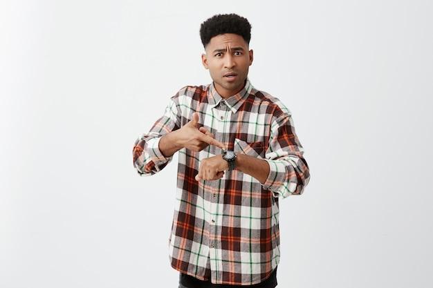 Wir kommen zu spät zum treffen. junger gutaussehender, hellbrauner, unglücklicher kerl mit afro-frisur in kariertem, stilvollem hemd, der auf eine handuhr zeigt und seinem mitbewohner sagt, er solle sich beeilen.