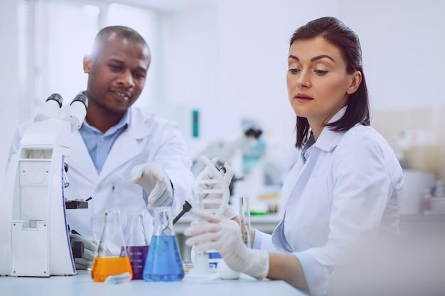 Wir lieben biologie. konzentrierter erfahrener forscher, der einen test durchführt, und sein kollege, der ihm hilft