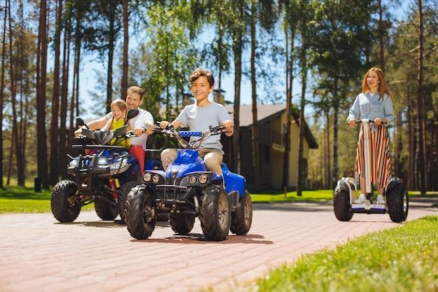 Wir lieben das fahren. erfreute süße kinder, die zeit mit ihren eltern verbringen und geländefahrzeuge fahren