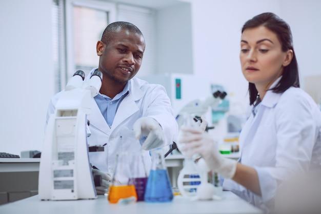 Wir lieben die wissenschaft. entschlossener erfahrener forscher, der einen test durchführt, und sein kollege, der ihm hilft