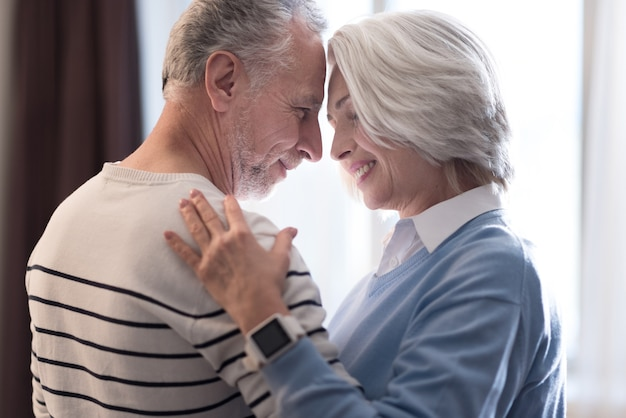 Wir lieben einander. fröhliches, friedliches ehepaar im alter, das zu hause tanzt, während es sich ansieht und umarmt
