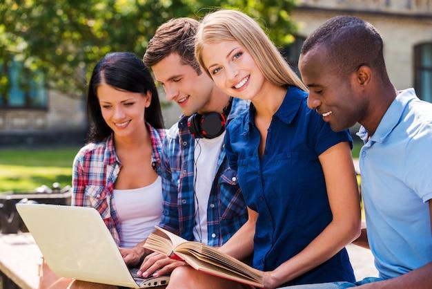 Wir lieben es, zeit miteinander zu verbringen. vier glückliche junge leute, die laptop betrachten und lächeln, während sie zusammen im freien sitzen