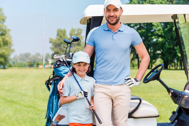 Wir lieben golf! lächelnder junger mann, der seinen sohn umarmt, während er einen golfwagen lehnt
