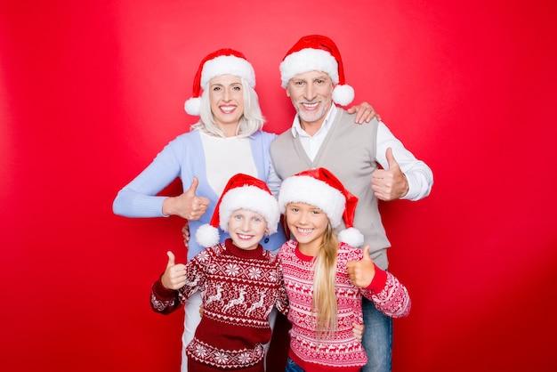 Wir mögen heilige magie x mas zeit! vier verwandte verbinden sich isoliert auf dem roten raum, aufgeregte geschwister, opa, oma, in gestrickter niedlicher traditioneller kleidung, umarmend, gute geste zeigend