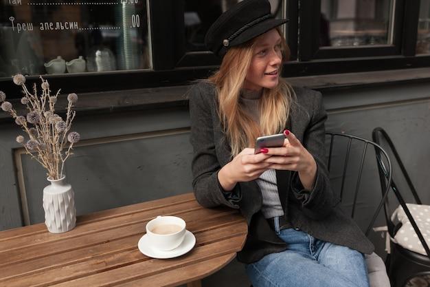 Wir sehen eine charmante junge hübsche blonde dame in warmen, eleganten kleidern, die im stadtcafé zu mittag isst, kaffee trinkt und mit ihren freunden auf dem smartphone plaudert