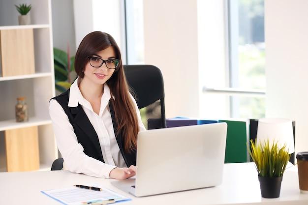 Wir sehen eine junge geschäftsfrau, die papierkram erledigt, während sie an einem schreibtisch im büro sitzt.