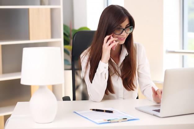 Wir sehen eine schöne junge geschäftsfrau, die papierkram erledigt, während sie an einem schreibtisch im büro sitzt.